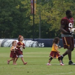 Clifton Geathers walks with some young fans after practice.
