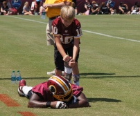 Redskins safety Duke Ihenacho lets a fan help him stretch before practice. Photo by Terri Russell.