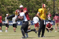 Running back Silas Redd Jr. takes a hit from head coach Jay Gruden. Photo by Terri Russell.