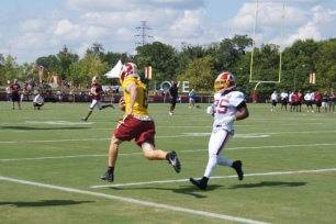 Kirk Cousins runs up the sideline. (Photo by Jake Russell)