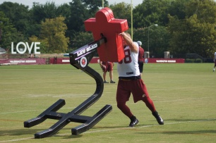 Fullback Elijah Wellman works on a blocking sled. (Photo by Jake Russell)