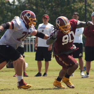 Defensive lineman Ziggy Hood runs by offensive guard Brandon Scherff in a blocking drill. (Photo by Jake Russell)