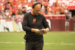 Maryland interim head coach Matt Canada looks at his play sheet. (Photo by Jake Russell)