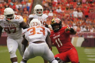 Maryland quarterback Kasim Hill slides before being hit by Texas linebacker Gary Johnson, who was ejected for targeting after the head-to-head collision knocked Hill's helmet off his head. (Photo by Jake Russell)