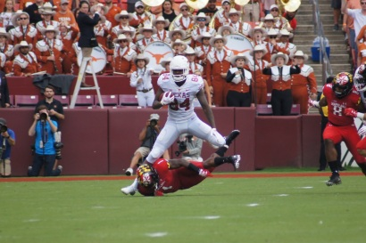Texas' Lil'Jordan Humphrey attempts to hurdle Maryland's DJ Turner. (Photo by Jake Russell)
