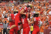 Terps running back Tayon Fleet-Davis is bombarded by teammates celebrating his touchdown. (Photo by Jake Russell)