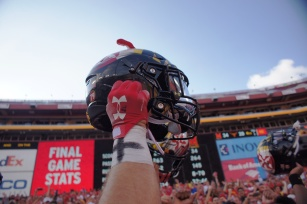 A Maryland player holds his helmet to the sky after the Terrapins' surprise victory over the Texas Longhorns. (Photo by Jake Russell)