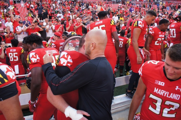 Maryland interim coach Matt Canada embraces offensive lineman Johnny Jordan. (Photo by Jake Russell)